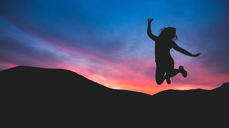 Silhouette photo of woman jumping against the mountain