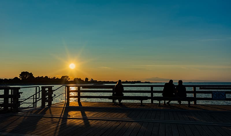 People standing on wooden dock during sunset