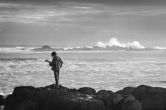 Person near body of water in grayscale photography