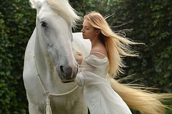Woman in white long sleeve shirt standing beside white horse during daytime