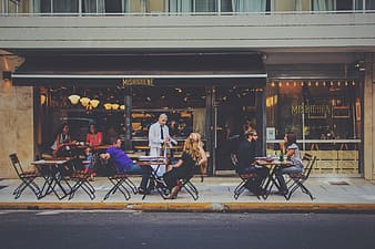 People sitting on cafe front with table setting during daytime
