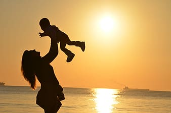 Silhouette lifting her baby upward near sea during sun set