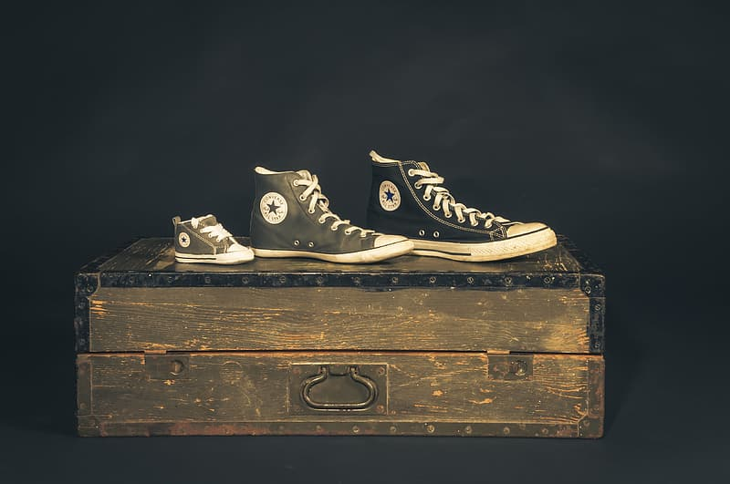 Three unpaired Converse All-Star shoes on wooden trunk