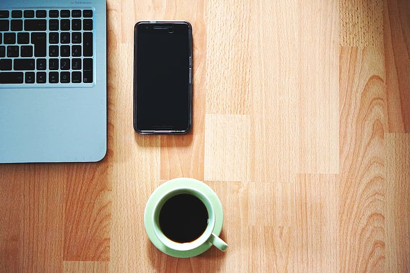 Green ceramic mug filled with coffee on green saucer beside black Android smartphone