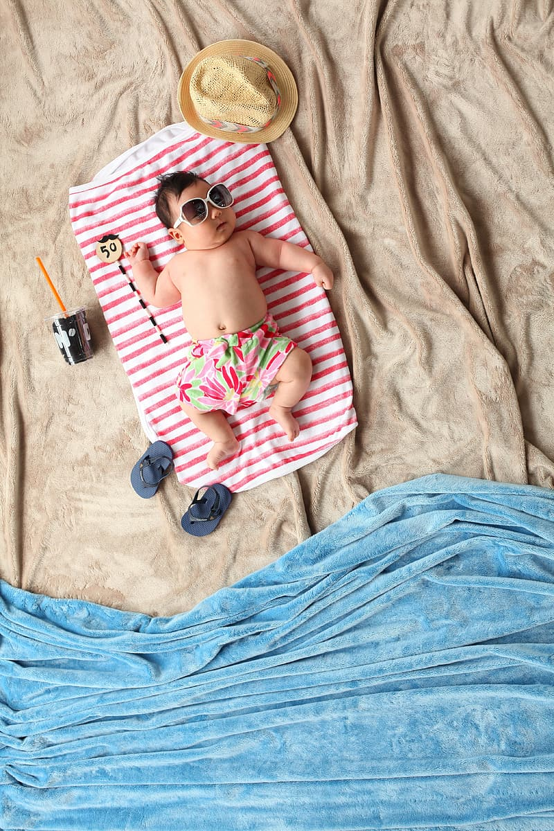 Baby lying on red and white blanket with summer-themed photography