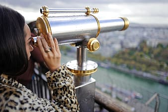 Woman taking a peek on coin operated telescope
