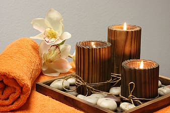 Three brown wooden tealight candle holders and white orchid flowers