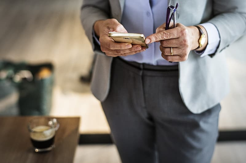 Person wearing suit jacket holding smartphone