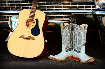 Brown dreadnought acoustic guitar beside pair of cowboy boots