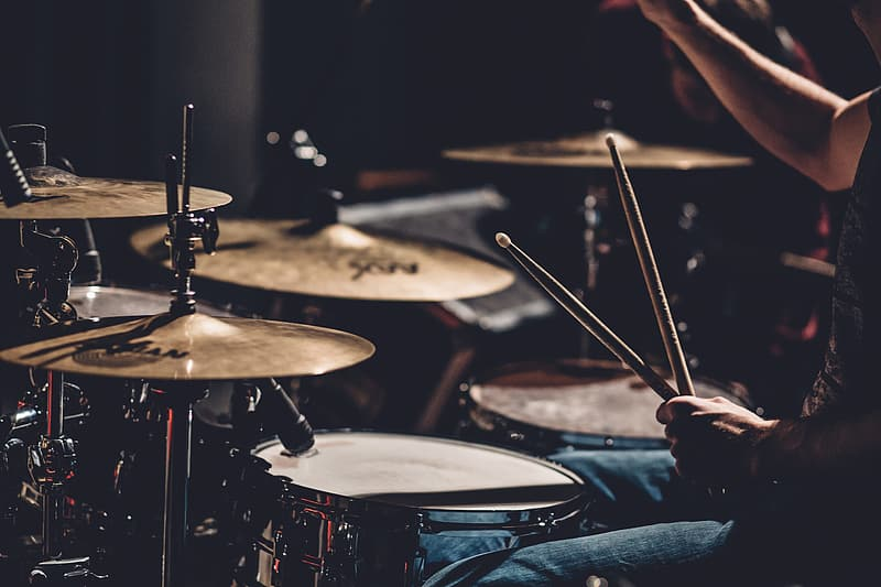 Person playing drum set in grayscale photography