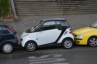 White Smart compact car parked on road side
