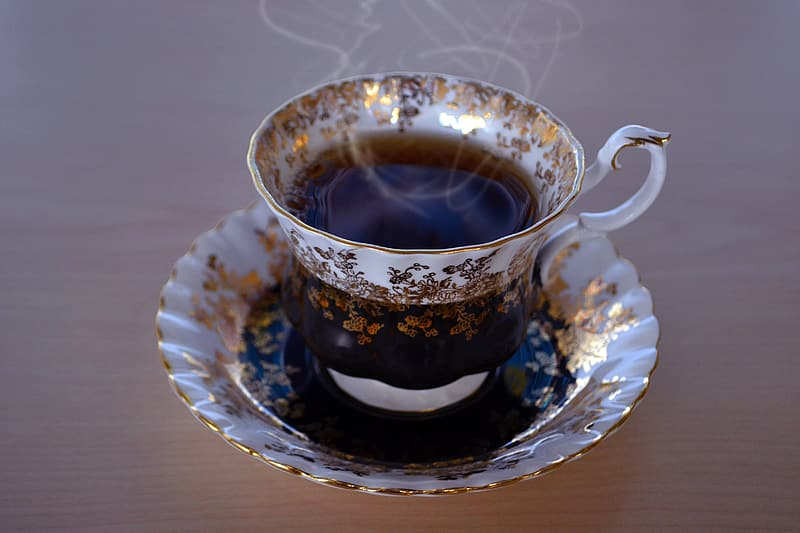 White and gold floral ceramic teacup filled with tea on top saucer