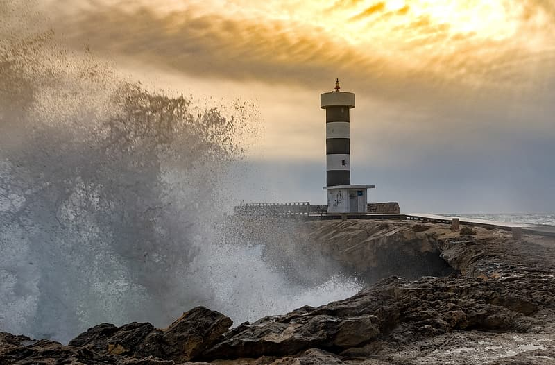 White and black lighthouse on rocky shore during sunset