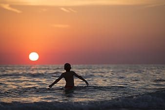 Boy on body of water during sun set