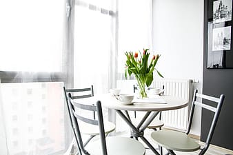 Round white dining table with four ladderback chairs