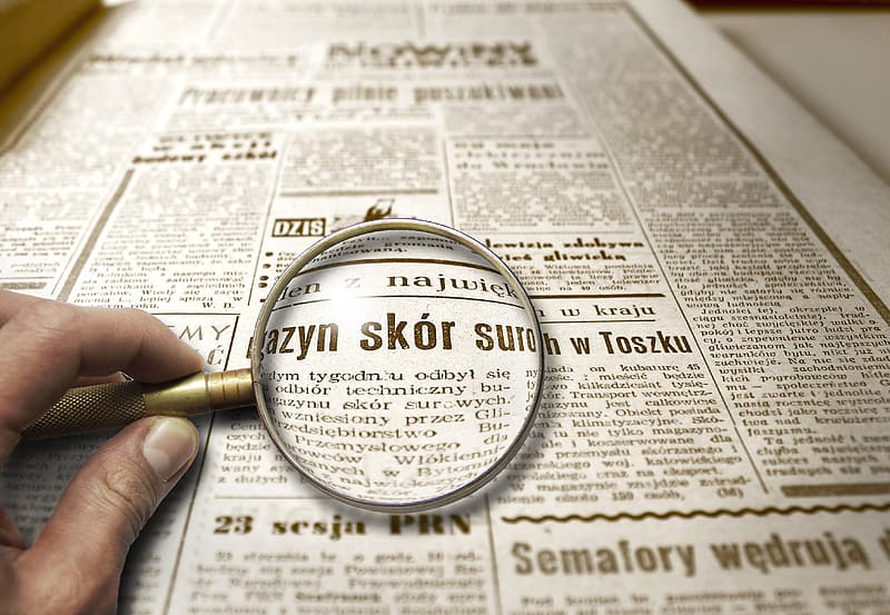 Silver magnifying glass on newspaper