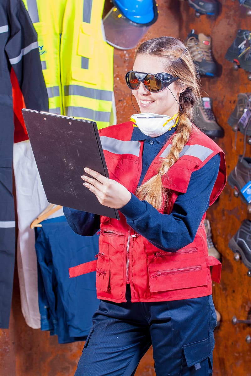 Woman in red jacket holding white tablet computer