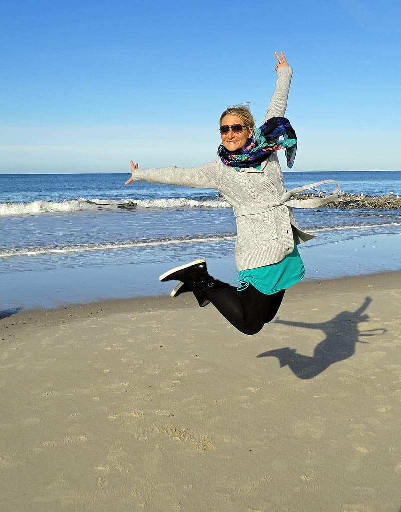 Woman jumping on near body of water