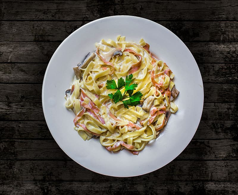 Pasta on round plate on brown wooden table