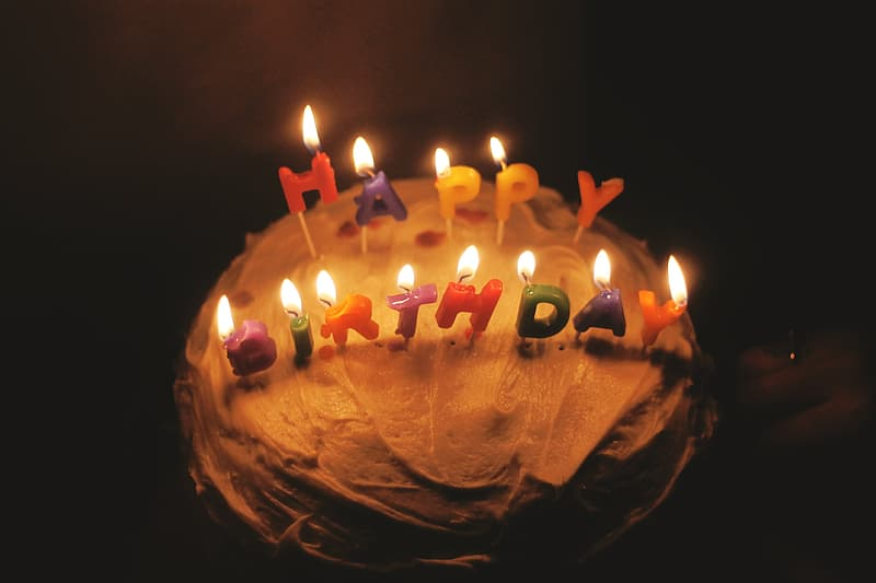 Orange cake with multicolored happy birthday candles with flames