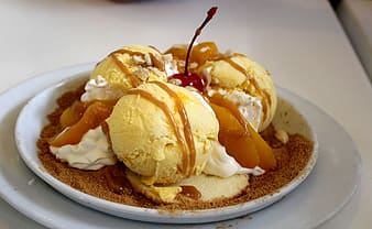 Ice cream with caramel and cherry on round white ceramic plate