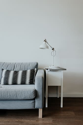 White task light on white side table beside blue sofa