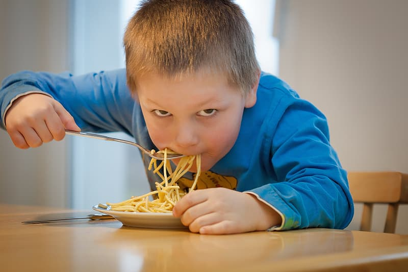 Boy in blue sweatshirt eating pasta on brown wooden table during daytime