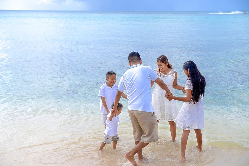 Family holding hands circle on seashore at day time
