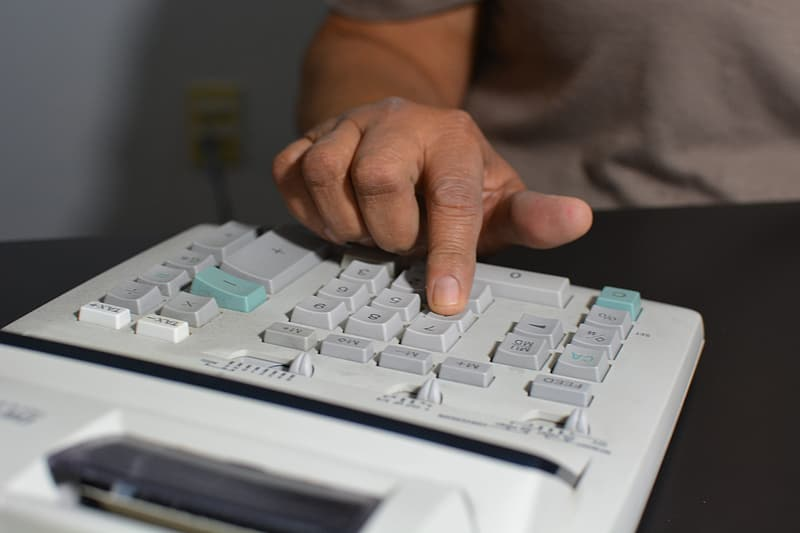 Person touching gray and white calculator