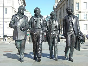Four men walking on street statues