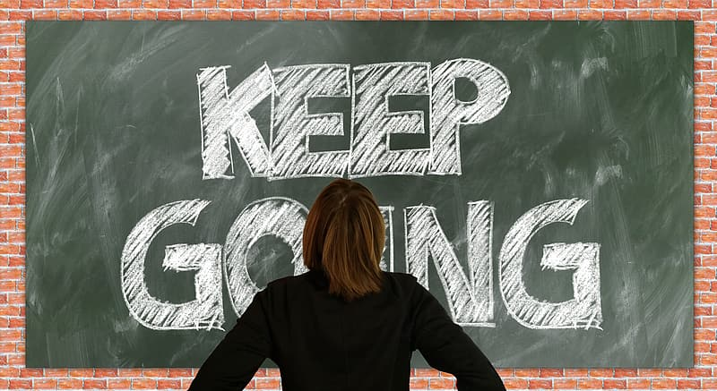 Person standing in front of green chalkboard with Keep Going text
