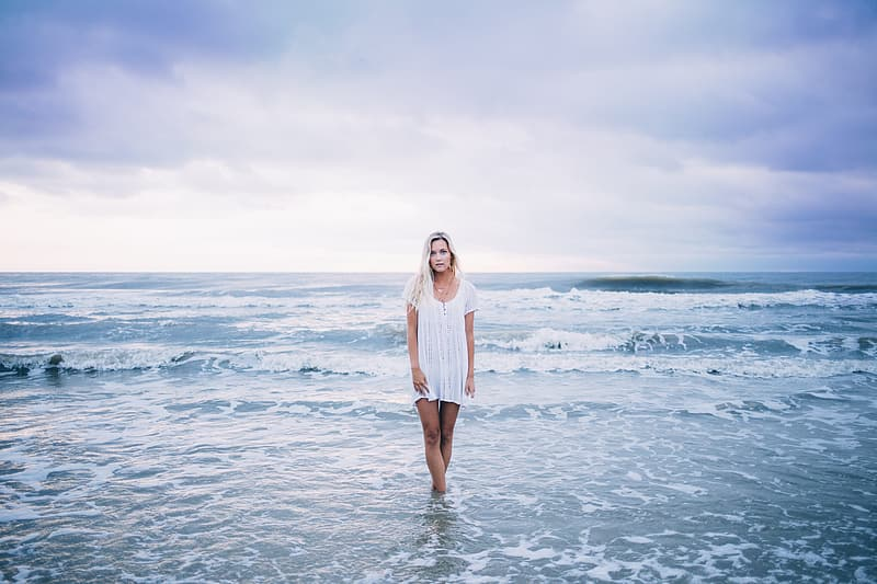 Woman in white long sleeve dress standing on sea water during daytime