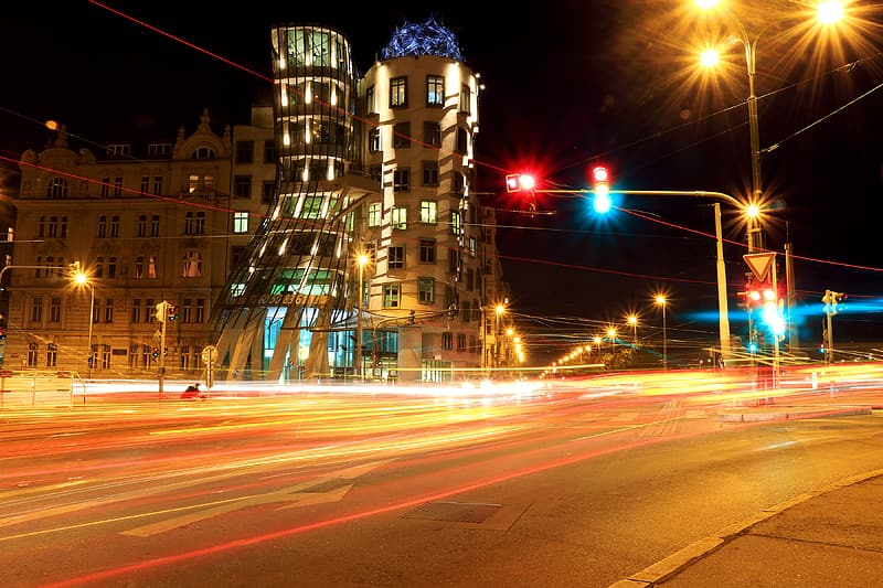 Time lapse photography of vehicle passing on road in front of concrete building at night time
