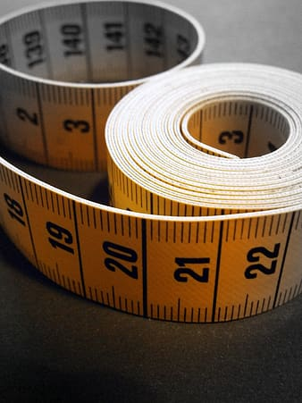 Yellow and black tape measure on gray surface