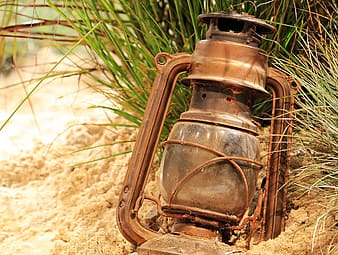 Brown gas lantern on sand during daytime