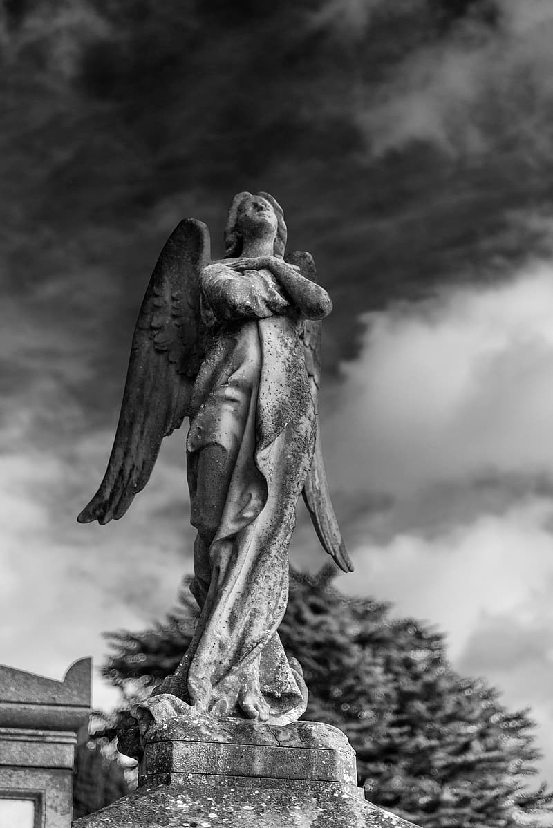 Gray angel statue under cloudy sky