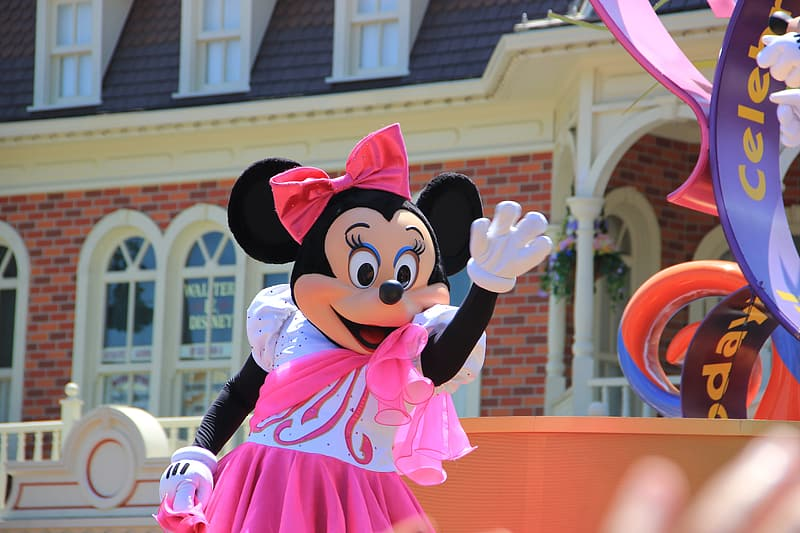 Minnie Mouse mascot waving on her right