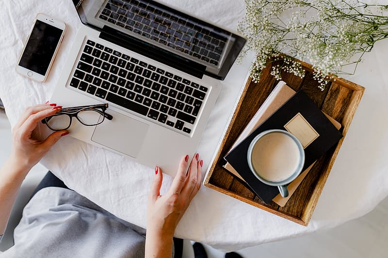 A woman works at a desk with a laptop and a cup of coffee