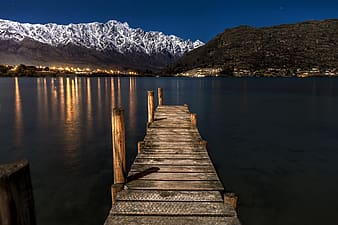Brown wooden dock on lake near snow covered mountain