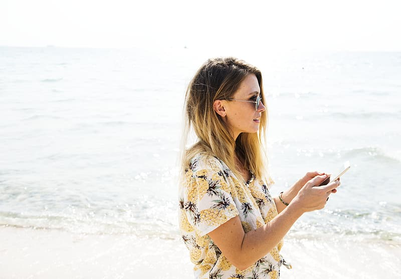 Woman wearing white and multi-colored floral shirt standing near the shore