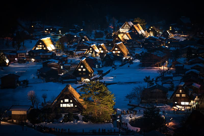Snow covered town with lights during night time