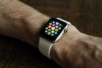Person wearing space gray Apple Watch with white sports band