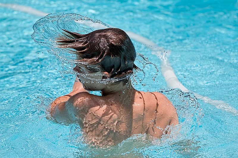 Boy with black hair spinning head in pool