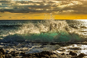 Sea waves crashing on shore during sunset