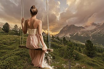 Woman in maxi dress sitting on swing facing mountains
