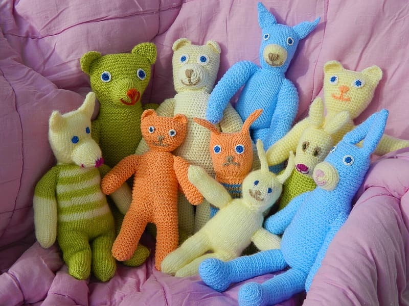 Assorted knitted plush toys on pink comforter