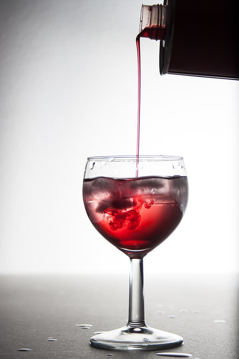 Poured red liquid in clear glass wine