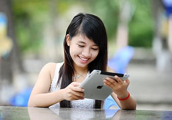 Woman holding iPad in front table