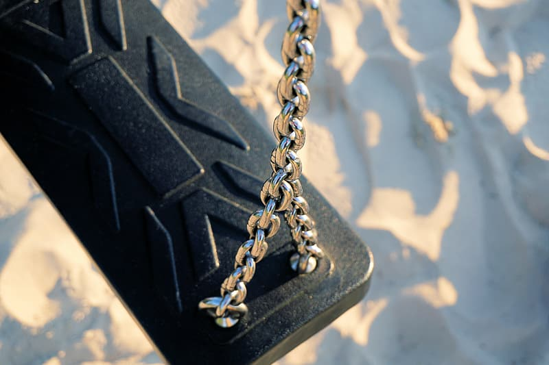 Gray metal chain with black case near blue and white surface