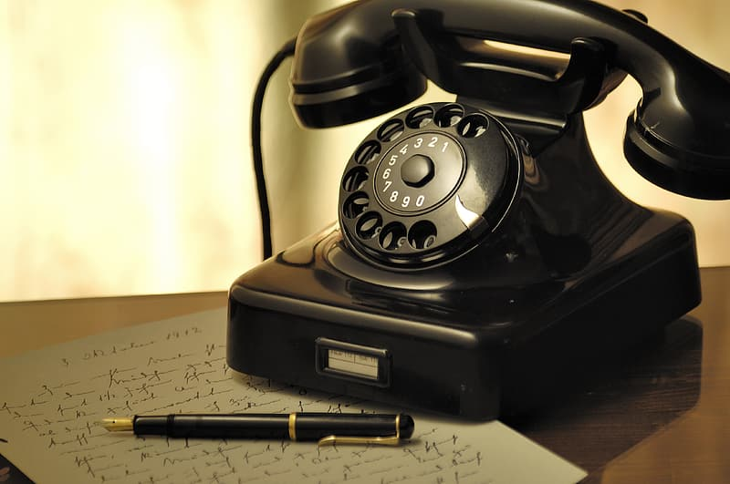 Black rotary phone beside black pen